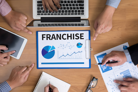 FRANCHISE Marketing Branding Retail Business team hands at work with financial reports and a laptop top view